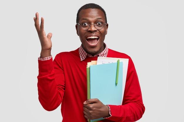 Überglücklicher erfolgreicher mann hebt die hand, ruft glücklich aus, freut sich, das schreiben der kursarbeit beendet zu haben, trägt die notwendige literatur