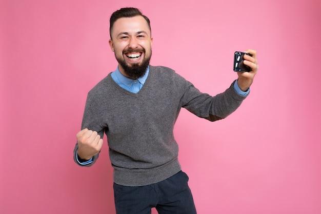 Überglücklicher glücklicher hübscher junger brünetter unrasierter mann mit bart, der alltäglichen grauen pullover trägt und