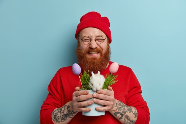 Überglücklicher glücklicher ingwermann, der nach der eiersuche zufrieden ist, topf mit weißem osterhasen im gras und in den bunten eiern hält, rotes outfit trägt, runde brille, feiert feiertag. frühlingszeitkonzept