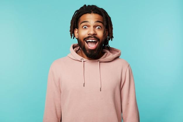 Überglücklicher junger hübscher brünetter bärtiger mann mit dreadlocks, die überraschend kamera mit großen augen und geöffnetem mund betrachten und über blauem hintergrund posieren