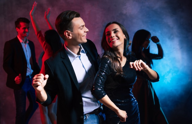 Überglücklicher junger mann in schickem outfit breitet sich beim tanzen mit seiner freundin die hände aus, die mit der linken hand über dem kopf posiert, lächelt und aufrichtig lacht