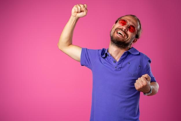 Überglücklicher lustiger bärtiger mann in gläsern, die erfolg feiern