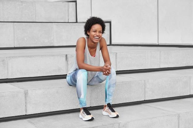Überglücklicher lustiger junge mit dunkler, gesunder haut, lockigem haar, sportkleidung, turnschuhen, lacht über etwas positives, hat nach dem sommertraining draußen ein gespräch mit einem freund, sitzt auf einer treppe