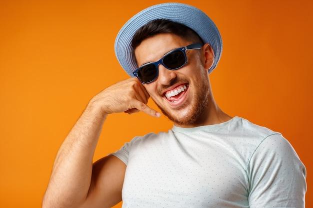 Überglücklicher mann mit strohhut und sonnenbrille zeigt mich geste