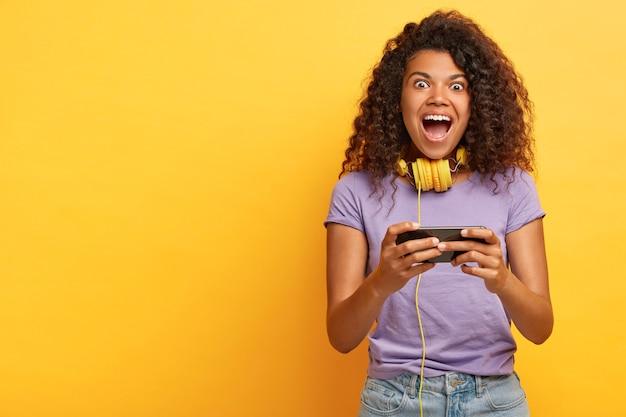 Überglückliches junges mädchen mit afro-frisur, spielt auf dem smartphone, lacht laut, trägt stereokopfhörer um den hals, trägt freizeitkleidung, isoliert auf gelb