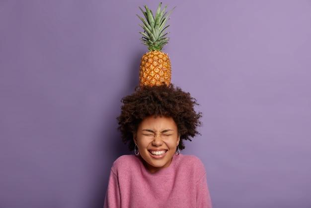 Überglückliches junges mädchen posiert mit leckerer ananas auf dem kopf, grinst glücklich, zeigt weiße zähne, hält die augen geschlossen, täuscht herum, hat lockiges buschiges haar