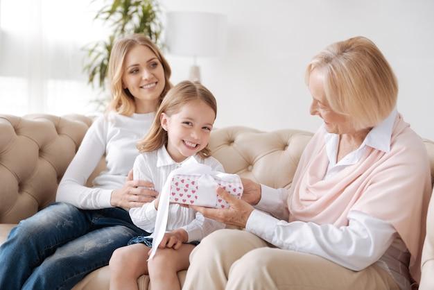Überglückliches kleines mädchen, das eine geschenkbox erhält, die mit einem weißen band von ihrer liebenden großmutter zusammengebunden ist, während ihre mutter sie umarmt und schaut