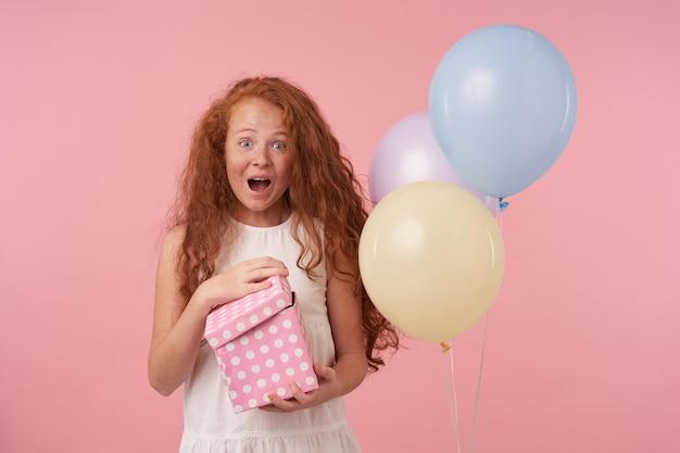 Überglückliches lockiges weibliches kind im eleganten weißen kleid, das über rosa hintergrund steht und geschenkbox in händen hält, aufgeregt ist, geburtstagsgeschenk zu erhalten, drückt wahre positive emotionen aus