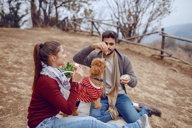 Überglückliches niedliches multikulturelles paar, das auf decke beim picknick sitzt und hund mit sandwich füttert. herbstsaison.