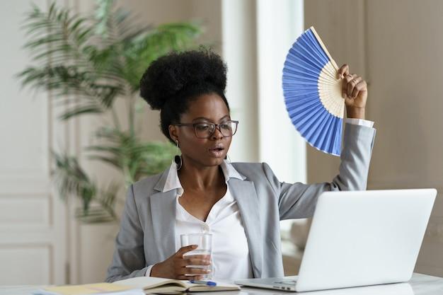 Überhitzter afrikanischer geschäftsfrau-wellenfan trinkt wasser am schreibtisch mit laptop oder zu hause