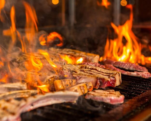 Überkochte fleischsteaks gehen auf dem grill in flammen auf