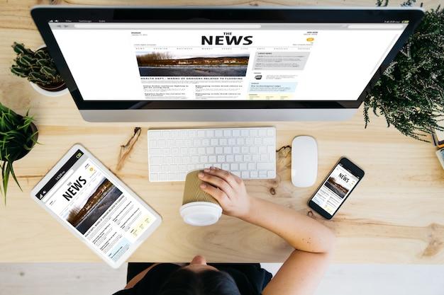 Überkopfansicht der frau, die kaffee trinkt und nachrichtenwebsite durchsucht