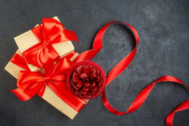 Überkopfansicht des nadelbaumkegels auf schönem geschenk auf dunklem hintergrund