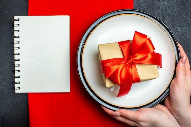 Überkopfansicht des nationalen weihnachtsmahlzeithintergrundes mit der hand, die leere teller mit bogenförmigem rotem band und einem notizbuch auf einer roten serviette auf schwarzem tisch hält