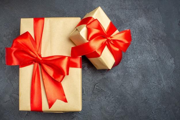 Überkopfansicht des weihnachtshintergrundes mit schönen geschenken mit bogenförmigem band auf der rechten seite auf einem dunklen hintergrund
