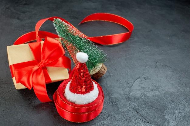 Überkopfansicht des weihnachtsmannhutes auf einer rolle des bandes und des schönen geschenkweihnachtsbaums auf dunklem hintergrund