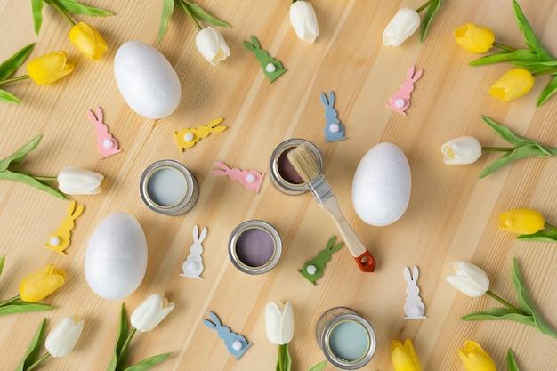 Überkopfansicht, die ostereier auf hölzernem tischfarbpinselkonzept des traditionellen frühlings-sommerzeit-farbhintergrunds malt