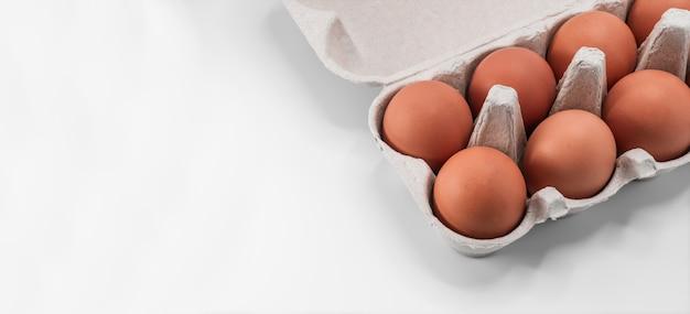 Überkopfansicht von braunen hühnereiern in einem offenen eierkarton lokalisiert auf weißem hintergrund
