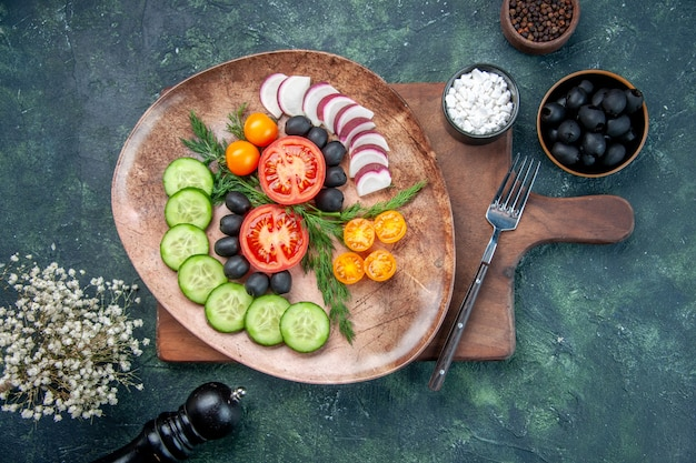 Überkopfansicht von frisch gehacktem gemüse in einer braunen platte auf hölzernen schneidebrettoliven in der schüssel-salz-knoblauchblume auf gemischtem farbhintergrund