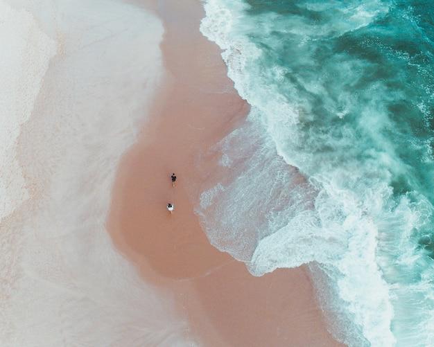 Überkopfaufnahme der leute, die einen sonnigen tag an einem sandstrand nahe schönen wellen des meeres genießen