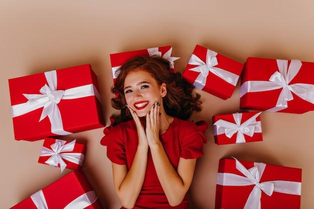 Überkopfaufnahme der reizenden ingwerfrau, die geburtstag genießt. gut gelauntes rothaariges weibliches model, das neben geschenken auf dem boden liegt.
