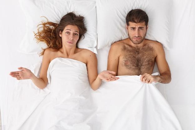 Überkopfaufnahme der verwirrten frau und ihres mannes haben sexuelle probleme im bett, missfallene mimik, liegen unter weißer decke. der mensch hat impotenz, erektionsstörungen. tagesleben familie probleme konzept