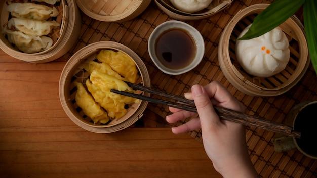 Überkopfaufnahme der weiblichen hand mit stäbchen, die bereit sind, gedämpfte knödel zu essen, die auf bambussitzer dienen