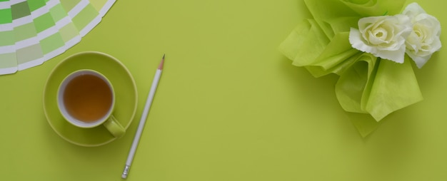 Überkopfaufnahme des arbeitsbereichs mit kopierraum, teetasse, farbigem farbfeld und dekoration auf grünem tisch
