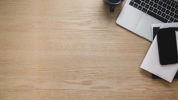 Überkopfaufnahme des arbeitsbereichs mit telefon, laptop, kopierraum und anderem büromaterial auf holztisch