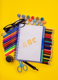 Überkopfaufnahme des briefpapiers auf gelbem schreibtisch, schulbürobedarf