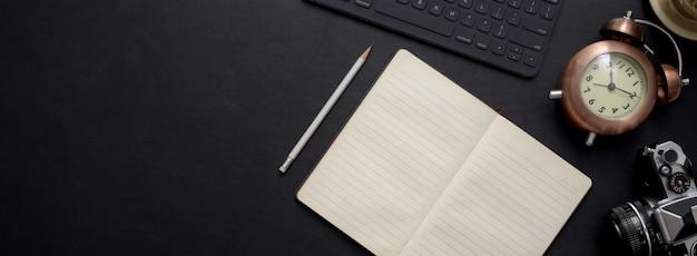 Überkopfaufnahme des dunklen konzeptschreibtischs mit leerem notizbuch, digitalem gerät und dekoration