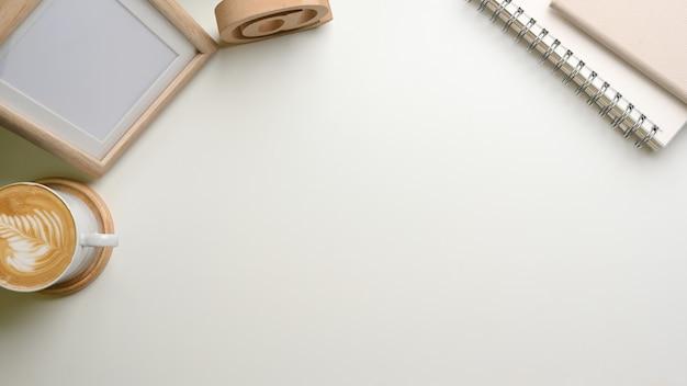 Überkopfaufnahme des einfachen arbeitsbereichs mit kaffeetassenmodell-notizbüchern und kopierraum auf weißem schreibtisch