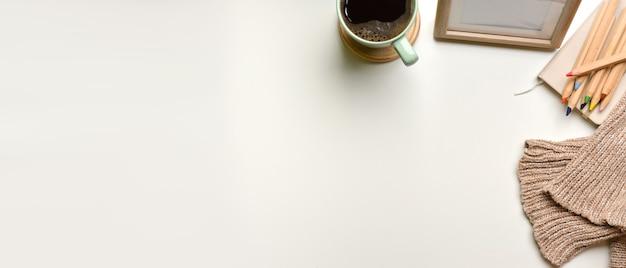 Überkopfaufnahme des einfachen arbeitsbereichs mit tassenrahmenfarbstiftpullover und kopierraum