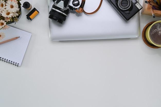 Überkopfaufnahme des fotografenarbeitsbereichs mit laptop, kamera, notizbuch, kaffeetasse und kopierraum auf weißem tisch.
