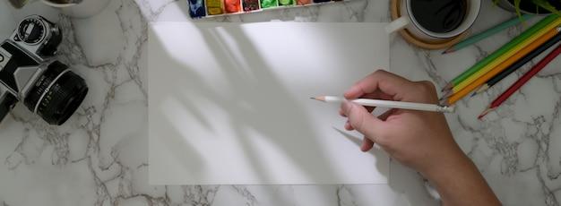 Überkopfaufnahme des männlichen künstlers, der auf skizzenpapier mit malwerkzeugen zeichnet