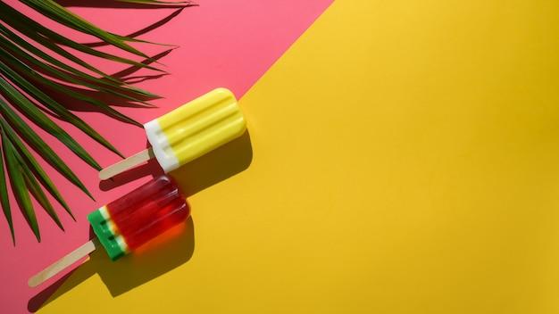 Überkopfaufnahme des minimalen bunten sommerkonzepts mit eis am stiel auf rotem und gelbem hintergrund