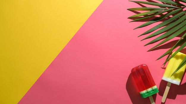 Überkopfaufnahme des minimalen sommerkonzepts mit eis am stiel auf rotem und gelbem hintergrund
