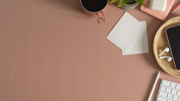 Überkopfaufnahme des modernen arbeitsbereichs mit büromaterial und kopienraum auf rosa tischhintergrund