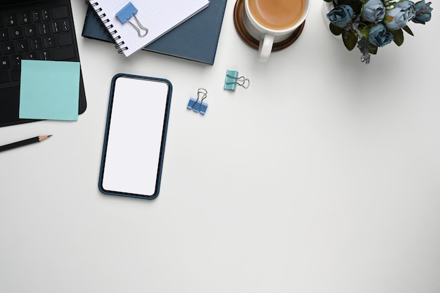 Überkopfaufnahme des smartphones mit leerem bildschirm, büromaterial und kopierraum auf weißem hintergrund.