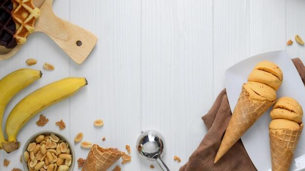 Überkopfaufnahme des sommerdesserts mit eistüten mit erdnussbutter-bananengeschmack