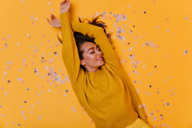 Überkopfaufnahme des sorglosen mädchens, das auf konfetti mit lächeln liegt. innenfoto des eleganten brünetten modells im gelben pullover.