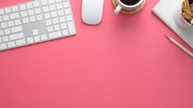 Überkopfaufnahme des stilvollen arbeitsbereichs mit computer, briefpapier, kaffeetasse und kopierraum auf rosa tisch