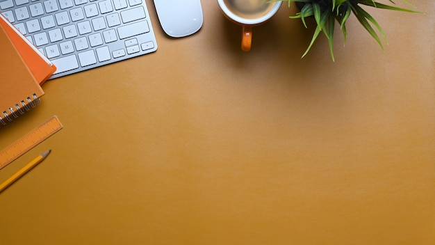 Überkopfaufnahme des stilvollen arbeitsbereichs mit notizbuch-, pflanzen-, tastaturanzeigenkopierraum auf gelbem hintergrund.