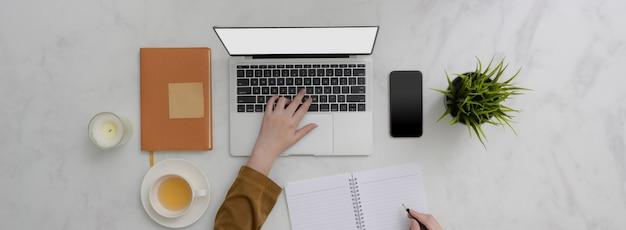 Überkopfaufnahme des studenten, der aufgabe mit laptop auf marmortisch tut