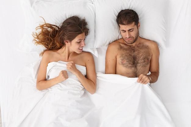 Überkopfaufnahme des unzufriedenen mannes hat probleme mit dem fortpflanzungssystem, erektiles versagen, leidet an impotenz, hoffnungsvolle frau unterstützt ihn, enttäuscht von winziger manngröße. sexuelle lebensstörung
