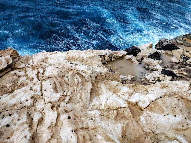 Überkopfaufnahme des weißen felsigen strandes in fuerteventura, spanien.