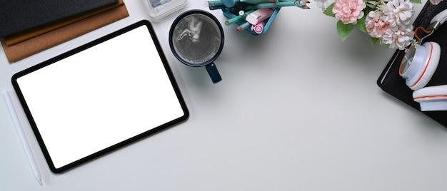 Überkopfaufnahme des weißen schreibtischs mit nachgebildetem digitalem tablett mit leerem bildschirm, kaffeetasse und büromaterial.