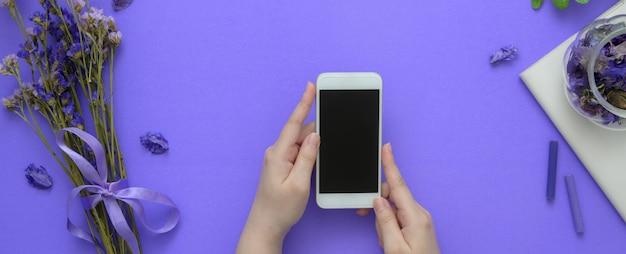 Überkopfaufnahme einer frau, die smartphone auf lila tisch hält
