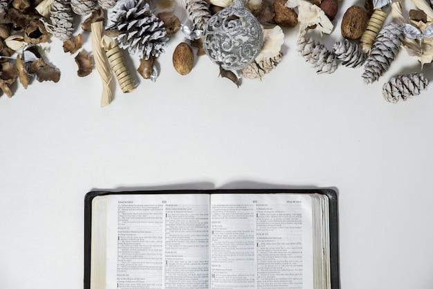 Überkopfaufnahme einer geöffneten bibel in der nähe von tannenzapfen und einer verzierung auf einer weißen oberfläche