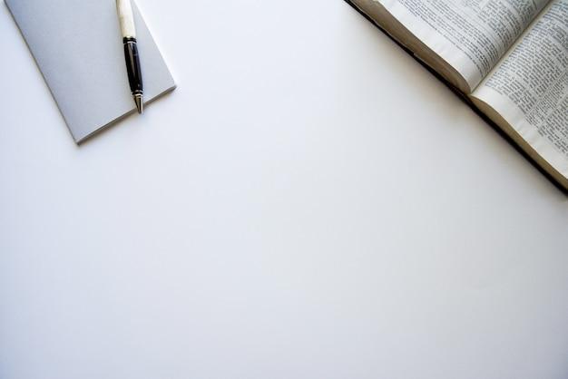 Überkopfaufnahme einer offenen bibel und eines notizblocks mit einem stift auf einer weißen oberfläche